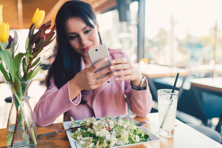 Young woman in restaurant photographing the food
